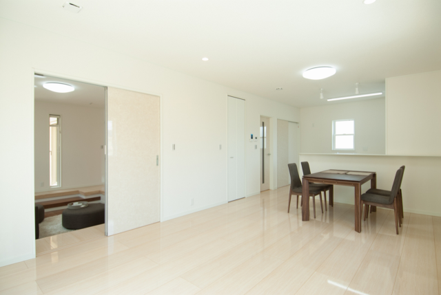 18帖のLDK。鏡面仕上げの床材が印象的。リビング側・キッチン側からも風が入ってくる窓の配置で快適に過ごせます。
